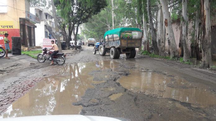 शहर में बरसात से टूटी सडक पर बने गडडे।